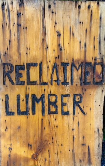 """""""reclaimed lumber"""" burned into board promoting reuse and recycling of old lumber"""
